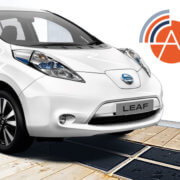 Photo of Nissan Leaf car on wireless charging pad with AMiCC logo